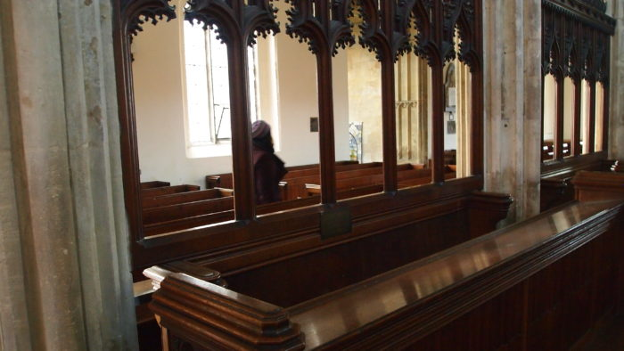 The choir stalls of a church, with a blurry human figure walking by in the background.
